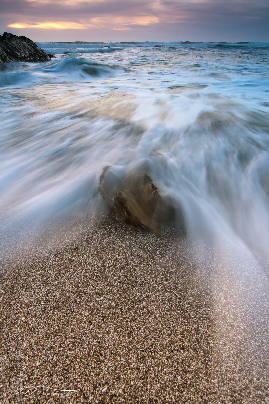The tide comes in and encroaches on a lone beach rock in Montaña De Oro State Park.