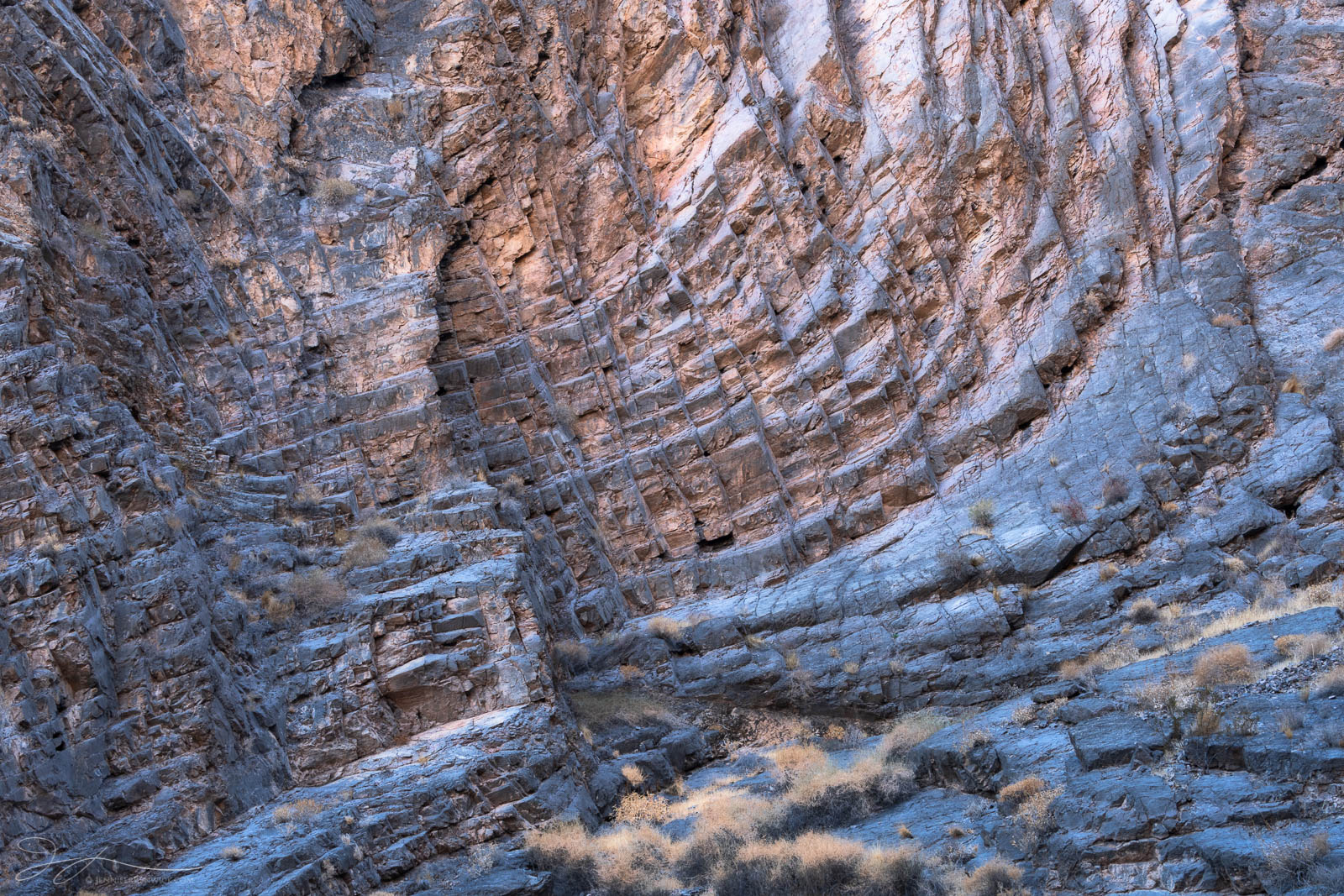 Layers and soft light adorn a remote canyon wall in the desert.