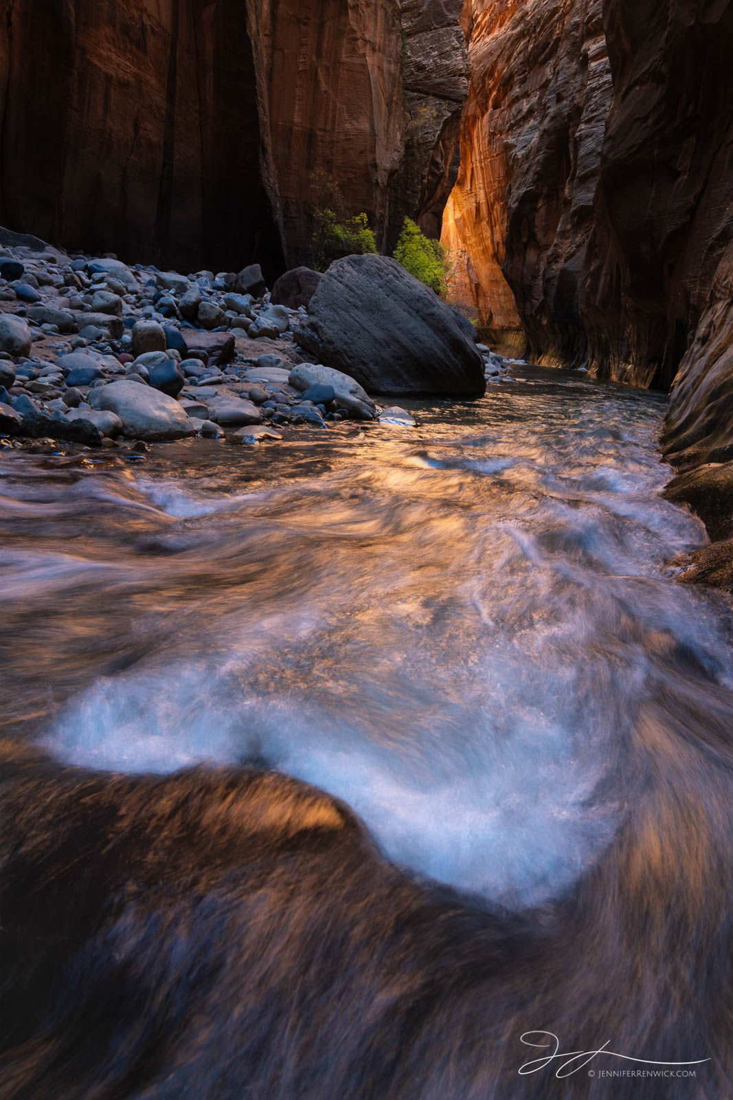 Water rushes down and reflects canyon glow in the Zion Narrows.