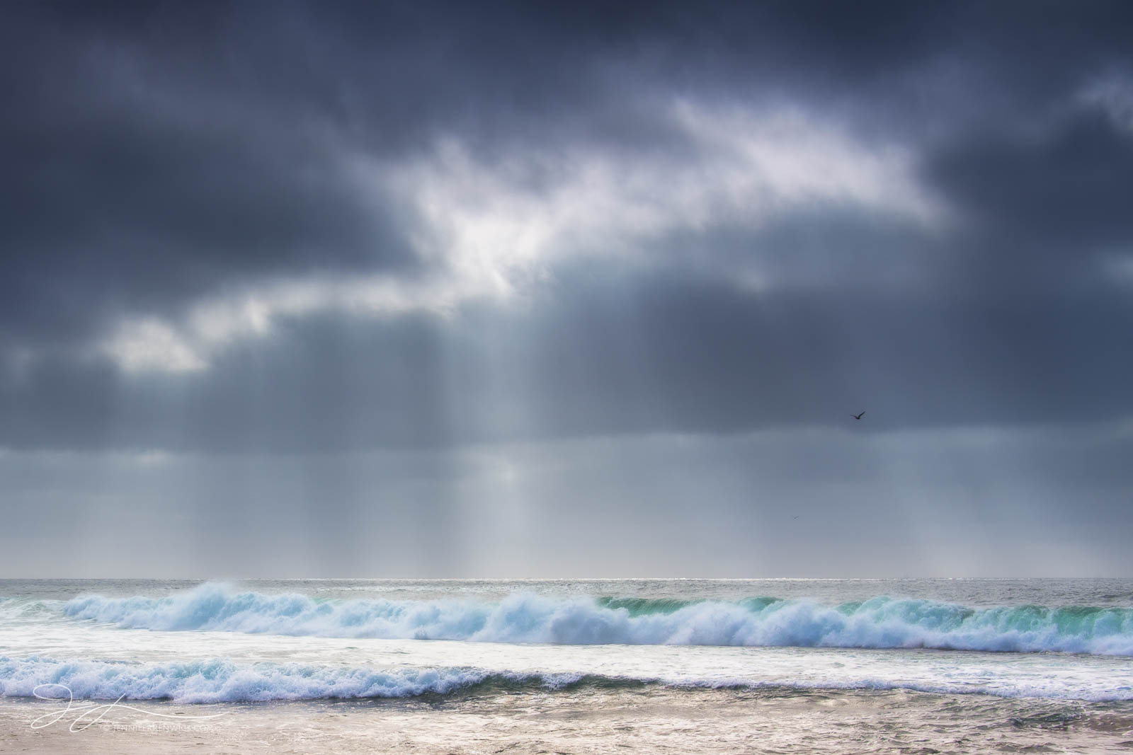 A storm clears as light beams shine down to the ocean near La Jolla, California.