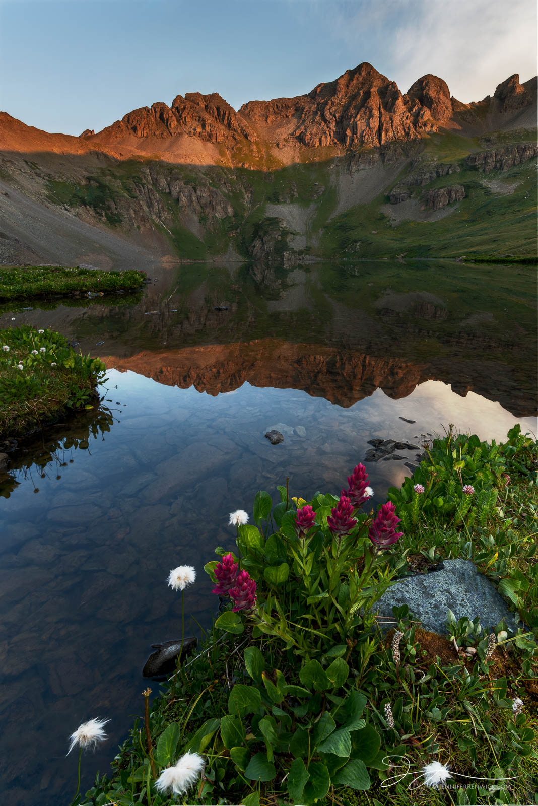 A high alpine lake catches the first light of morning.