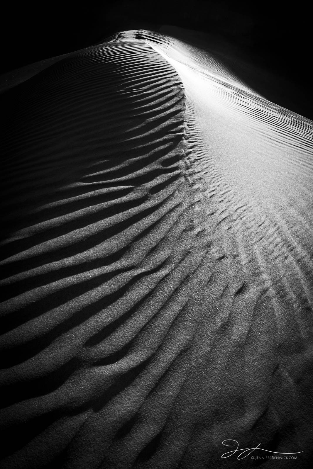 Sand ripples create a pattern on the slope of a dune.