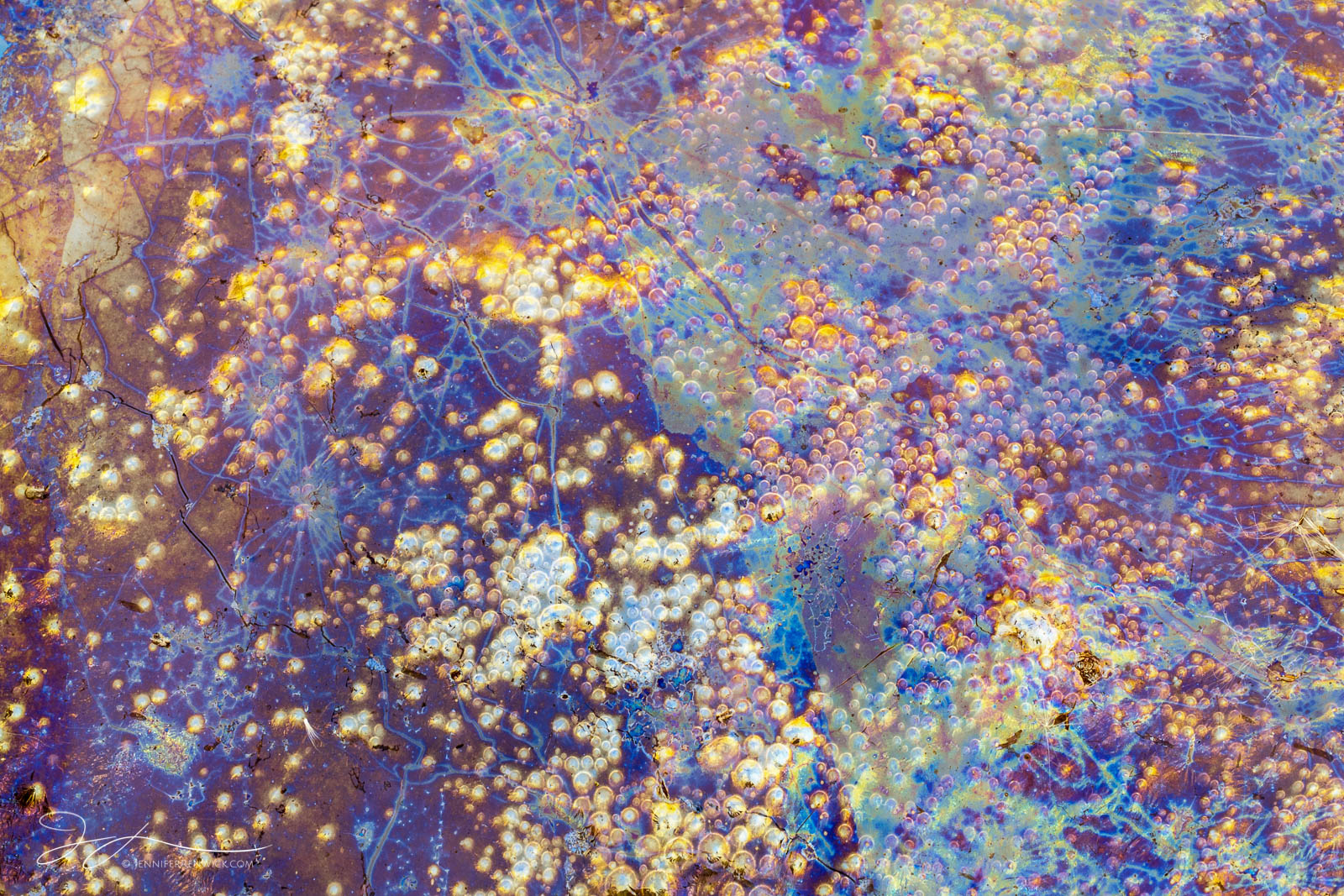Bubbles and color mix in a small puddle full of natural oils.