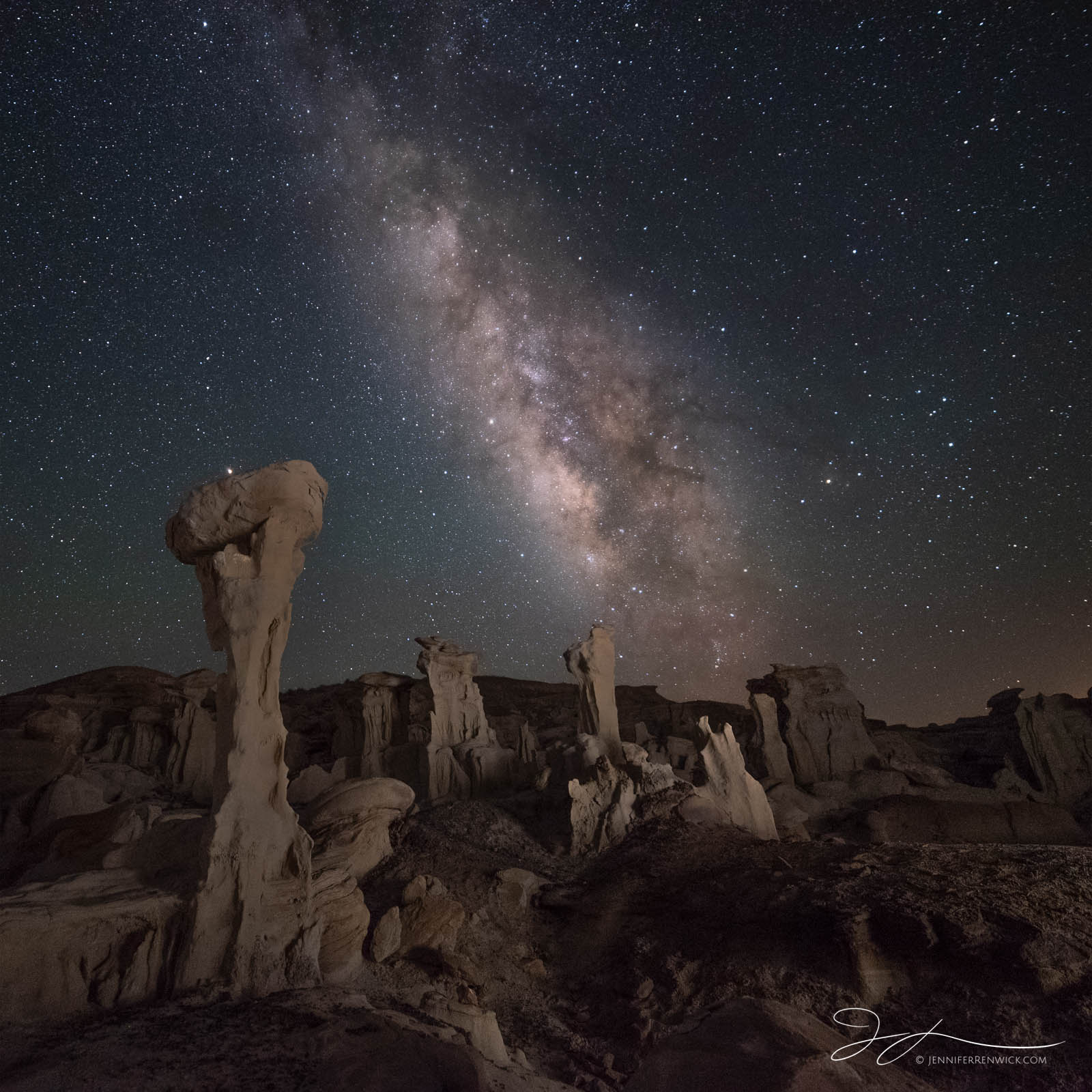 The Milky Way stretches over an area of badlands in New Mexico.