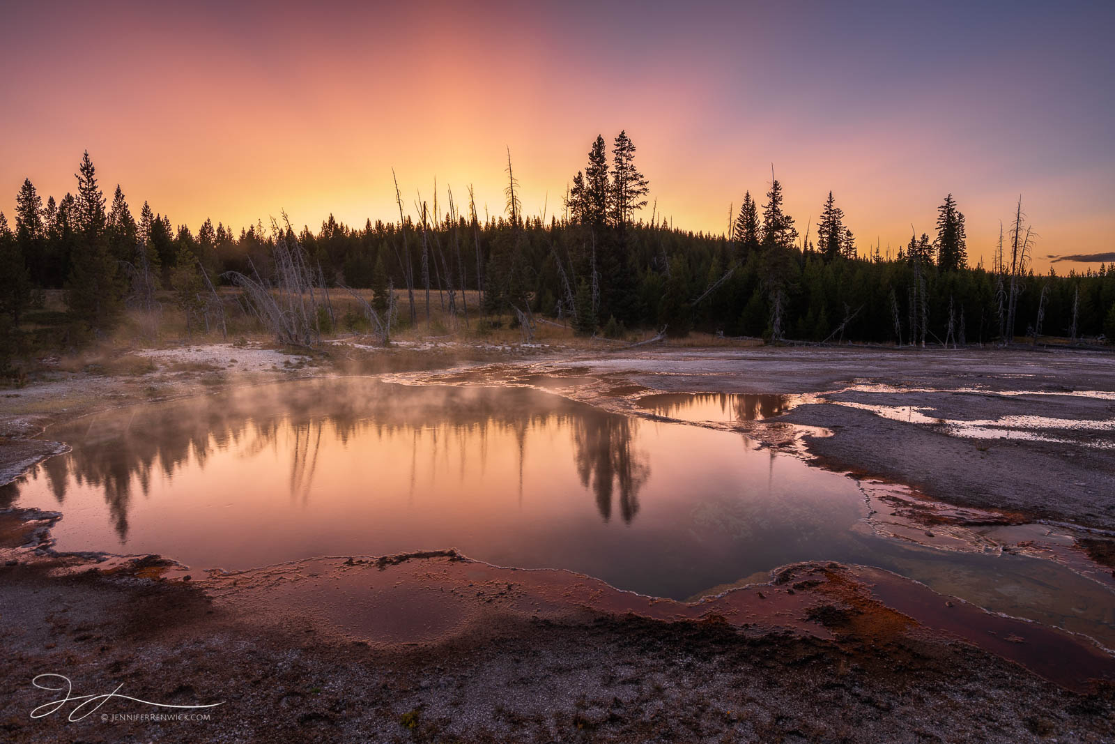 Sunset colors light up the sky and reflect into the Abyss Pool in West Thumb Geyser Basin.