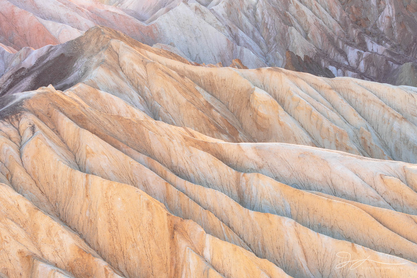 Layers and ridges in the badlands glow under the last light of the day.