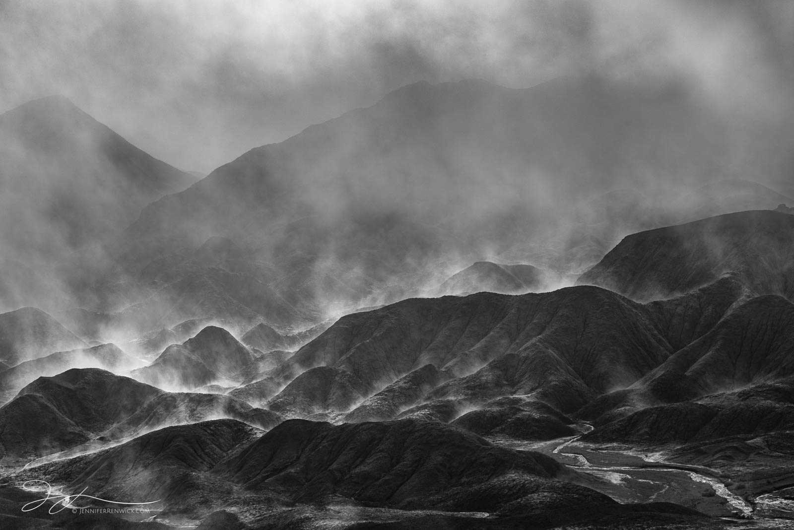 Sun backlights steam rising up from the badlands after a night of rain in Death Valley National Park.  This image is part of...