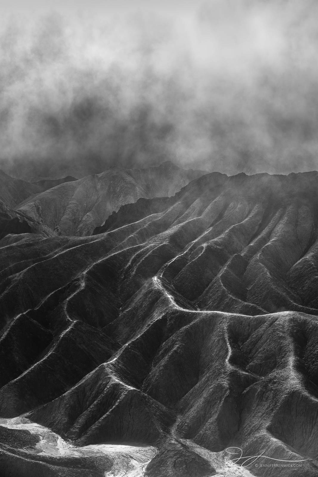 Sun breaks through to highlight the ridges as the fog clears in the badlands of Death Valley National Park.  This image is part...