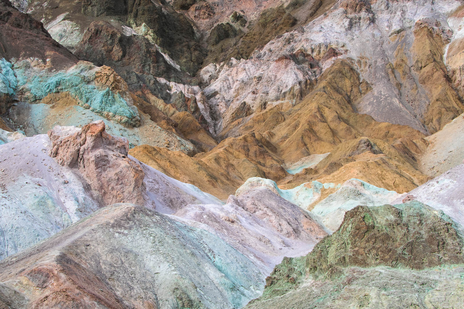 Colorful badlands in pastels of pink, green and brown glow in soft light.
