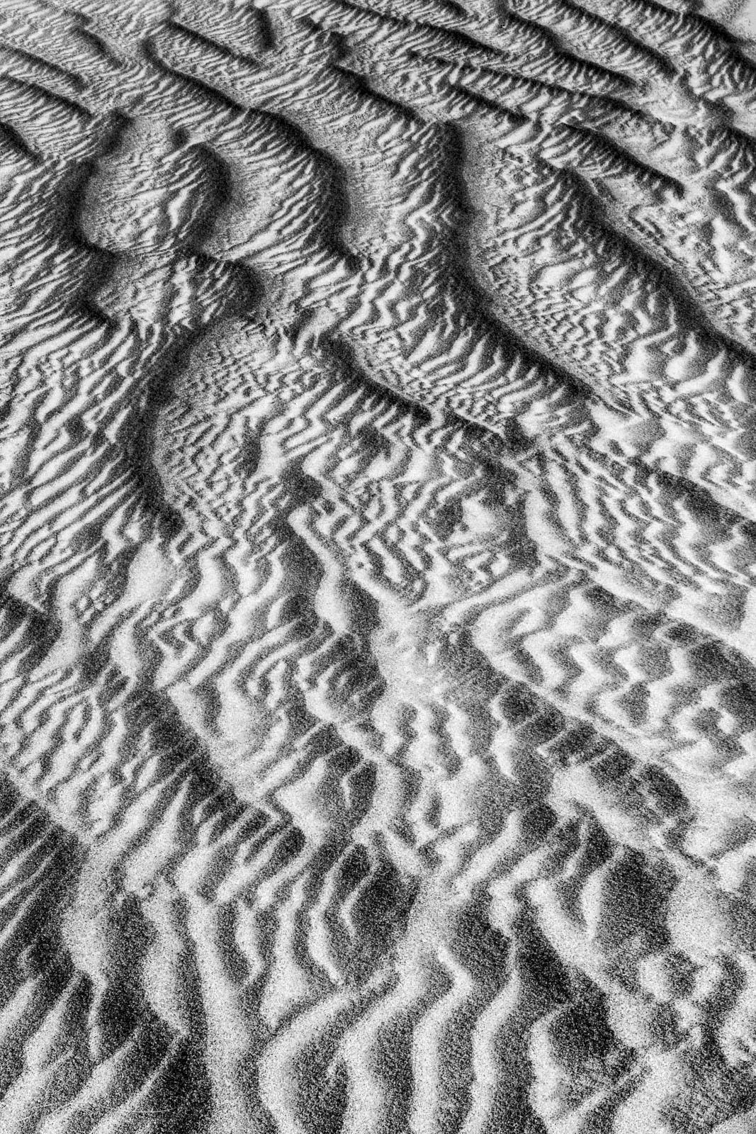 Sand patterns resemble aerial badlands on the desert floor.