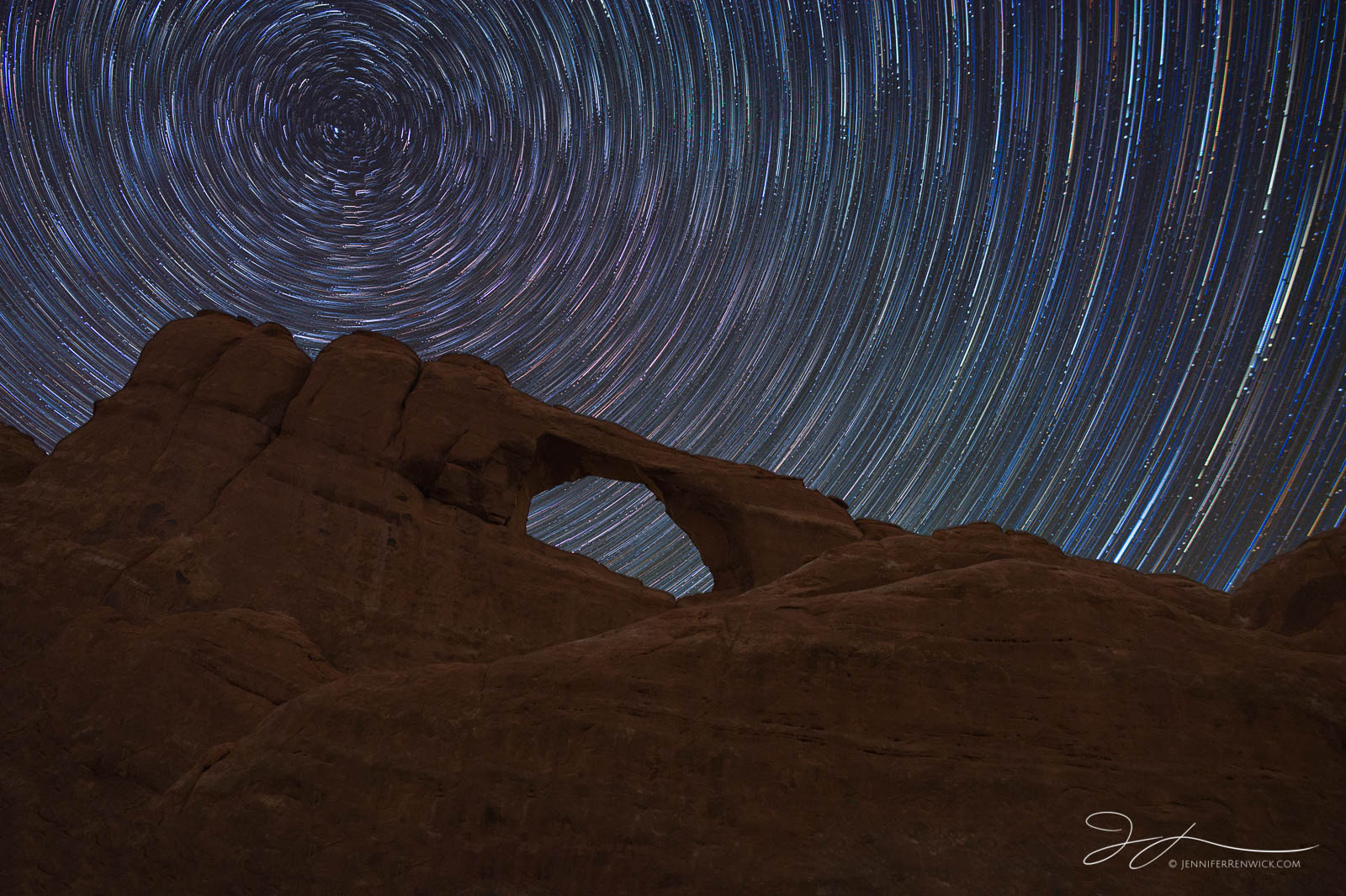 Colorful star trails form a vortex above Skyline Arch in Arches National Park.