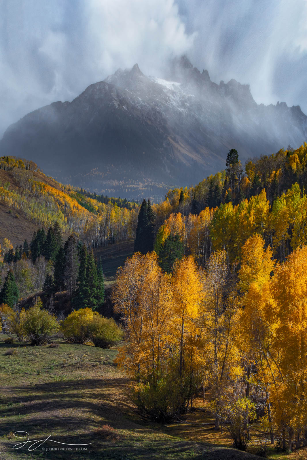 Mt. Sneffels rises above a grove of aspen trees while an autumn storm clears.