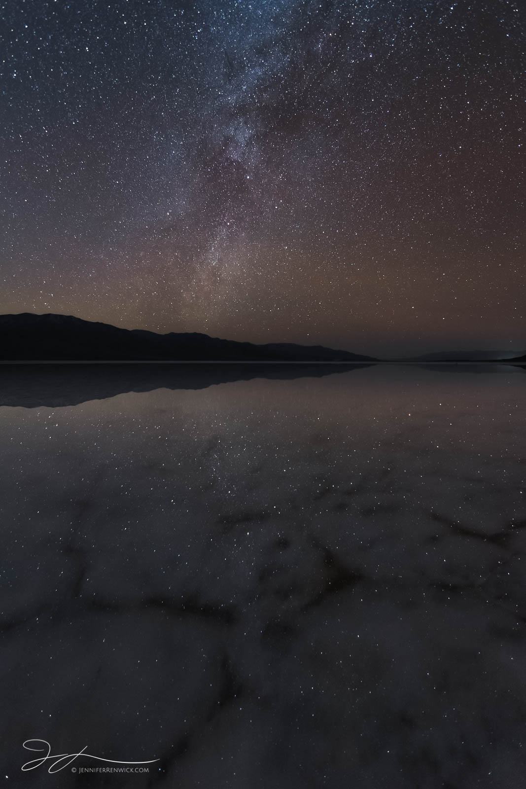 The night sky, complete with a meteor and winter milky way reflects onto a flooded Badwater Basin in Death Valley National park...