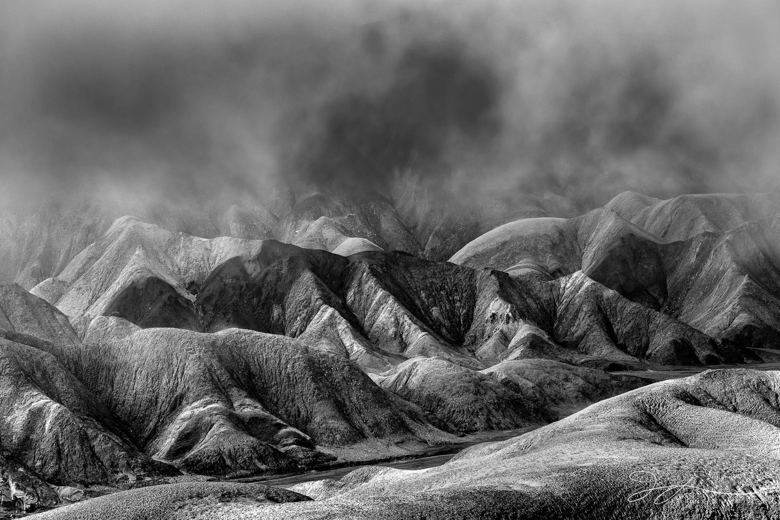 Sun breaks through and clears the fog after a rainy night in the badlands of Death Valley National Park.  This image is part...